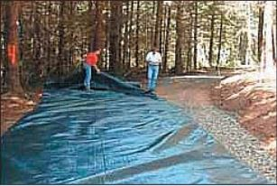 Geotextile fabric is laid over soft soil on a wet, rutted road.