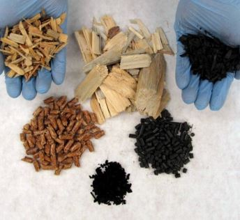 Figure 3. Five pyrolysis products plus pulp chips. Clockwise from top left: microchips from mixed conifer woody biomass, 3-inch pulp chips for reference (center), high carbon biochar resulting from pyrolysis at 1,000oC, pellets made from char, high surface area activated carbon made from char (biochar), and pellets made from wood Photo credit: Nate Anderson, USDA Forest Service